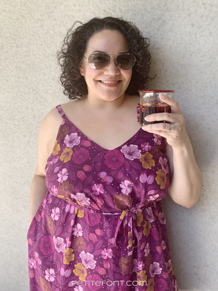 Curly haired Latina woman in sunglasses and a floral Sangria Misty Cami dress holding a glass filled with sangria. Text overlay reads PetiteFont.com