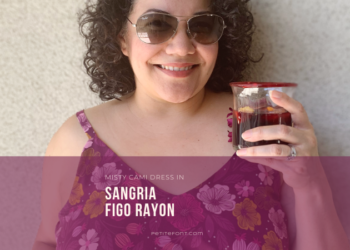 "Close up of a curly haired Latina woman in sunglasses and a floral purple dress holding a glass filled with sangria. Text overlay in a purple box reads ""Misty Cami Dress in Sangria Figo Rayon, PetiteFont.com"""