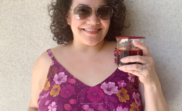 Close up of a curly haired Latina woman in sunglasses and a floral Sangria Misty Cami dress holding a glass filled with sangria. Text overlay reads PetiteFont.com