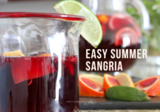 Glass on counter filled halfway with sangria, garnished with a lime wedge. Behind it is a bunch of cut up citrus, and a pitcher of the rest of the sangria. Text overlay reads Easy Summer Sangria, PetiteFont.com