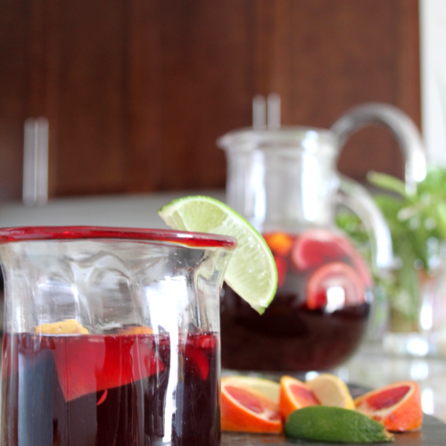 Glass on counter filled halfway with sangria, garnished with a lime wedge. Behind it is a bunch of cut up citrus, and a pitcher of the rest of the sangria