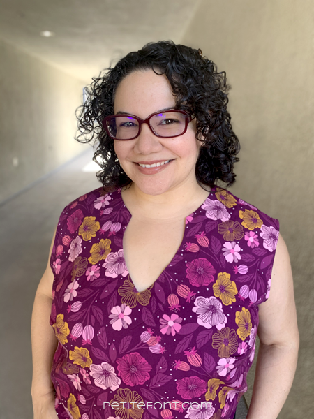 Latina woman with black curly hair and red glasses smiling at the camera in a floral open keyhole blouse