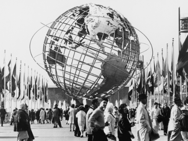 Black and white image of a crowd walking past the Unisphere, symbol of the New York 1964-65 World's Fair. Flushing Meadow Park, New York