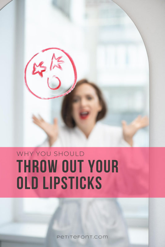 Image of a lipstick drawn face on a mirror reflecting a woman with her hands up. Black text overlay in a red box reads Why You Should Throw Out Your Old Lipsticks