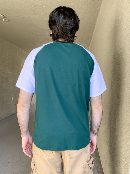 Back view of a dark haired man in a color blocked green and white Sunday V-neck and light brown cargo shorts