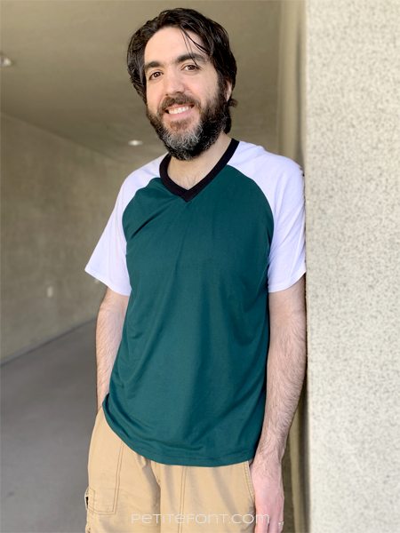 Dark haired man with a beard in a color blocked green and white Sunday V-neck and light brown cargo shorts