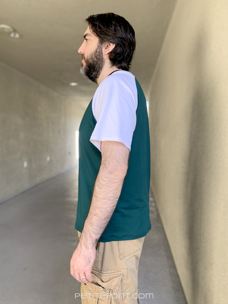 Side view of a dark haired man in a color blocked green and white Sunday V-neck and light brown cargo shorts