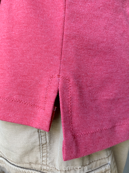 Zoomed in view of a split hem on a red handmade Game Day Jersey t-shirt