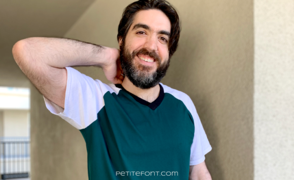 Dark haired man with a beard in a color blocked green and white Sunday V-neck t-shirt and light brown cargo shorts. He has a hand behind his neck and is smiling at the camera.