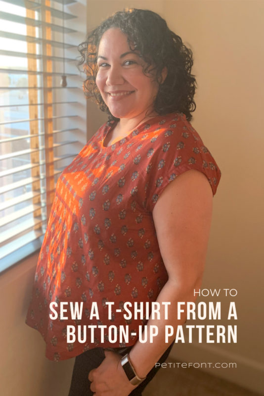 "Curly haired Latina woman in a dark rust colored floral woven t-shirt with one hand in her pocket standing in front of a window in the late afternoon. Text overlay reads ""how to sew a t-shirt from a button-up pattern, petite font dot com"""