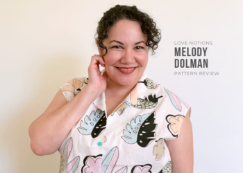 Paulette in front of a white wall, one hand up to her face, smiling. She is wearing a white button up camp shirt with a large scale kitschy pastel print of leaves and flowers. Text to the right of her reads Love Notions Melody Dolman Pattern Review.