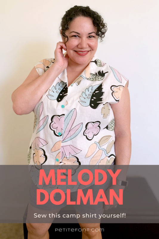 Paulette in front of a white wall and brown ottoman, one hand up to her face, smiling. She is wearing a white button up shirt with a large scale kitschy pastel print of leaves and flowers. Text overlay at the bottom in a grey box reads Melody Dolman: sew this camp shirt yourself!