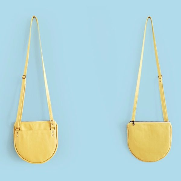 Front and back views of a yellow Pattern Scout Luna Crossbody purse up against a light blue wall