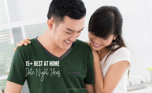 An Asian couple stands smiling and looking down in a white room. The man in a dark green v-neck t-shirt and woman with her arms around him looking over his shoulder is wearing a white t-shirt. Text reads 15+ best at home date night ideas