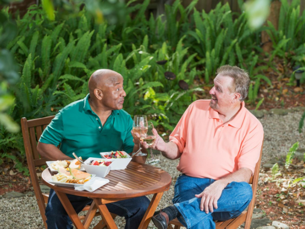Two older men, one bald and black and one white with a goatee, sharing wine and food at a table in a garden