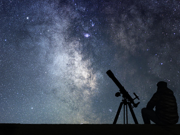 Silhouette of a person sitting near a telescope with the cosmos in the background