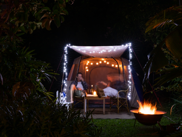 Night scene in back yard. A fire pit in the lower right corner with two people sitting in chairs under a lit canopy. A camping tent is behind them.