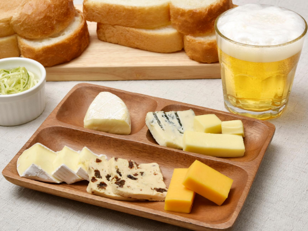 A platter of different cheeses and a beer and bread in the background