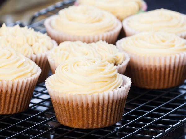 White frosted cupcakes cooling on a rack
