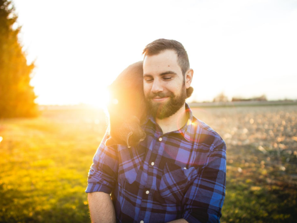 A picture of a bearded man in a plaid shirt with his eyes closed and a cat on his shoulder. The sun is low in the sky behind him, giving the entire picture a warm glow.