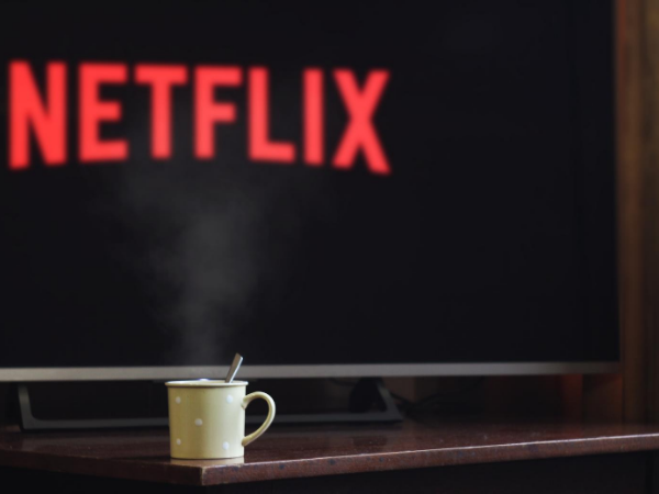 Coffee mug on table in front of a tv with the Netflix logo on it