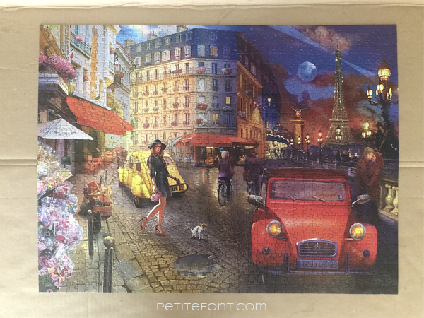 A completed puzzle on a cardboard, featuring an artist's rendition of a street scene from Paris including a woman walking a dog, two people on bikes, street cafes, lovers kissing by the river, and the Eiffel Tower in the background.