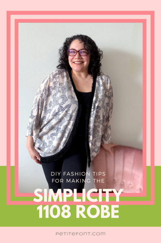 "Curly hair bespectabled woman in all black except a peach and black open robe, leaning against a pink chair. The picture is in a double pink frame on top of a pink and green background. Text overlay reads ""DIY fashion tips for making the Simplicity 1108 robe"""