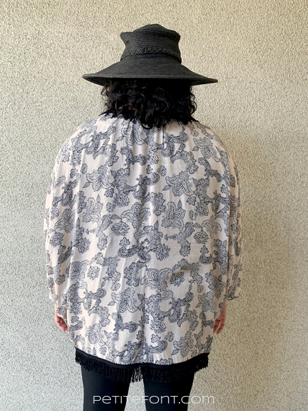 Paulette with her back to the camera wearing a black sun hat and a paisley version of Simplicity 1108 robe. The paisley pattern is on a light peach background.