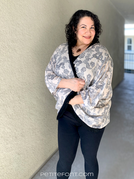 Paulette looking at the camera with her arms crossed in front of her. She is in a black shirt and pants with a peach paisley version of Simplicity 1108 over the top. She is crossing it closed in front of her.