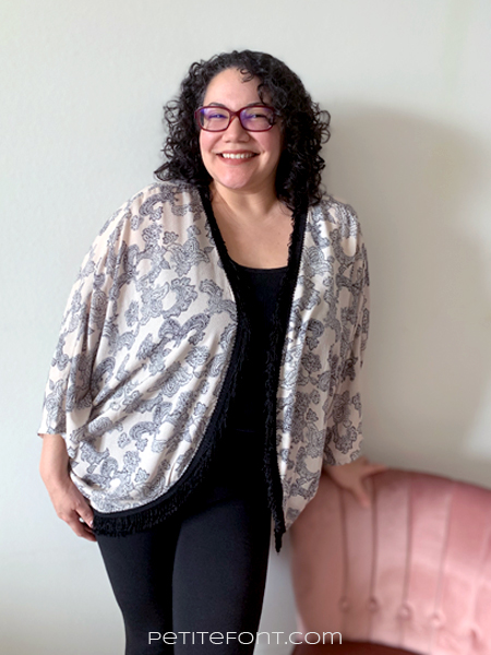 Paulette is smiling at the camera wearing red glasses and an all black outfit with a peach and black Simplicity 1108 robe over top. She is leaning a hand against a pink velvet chair.