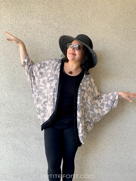 Paulette looking up to the left wearing a black hat and sunglasses with her arms out like a bird. She is in a black shirt and pants with a peach paisley version of Simplicity 1108 over the top.