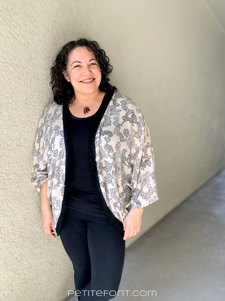 Paulette is leaning against a beige stucco wall smiling at the camera. She is wearing all black t-shirt and pants ensemble, with a peach and black paisley robe over top.