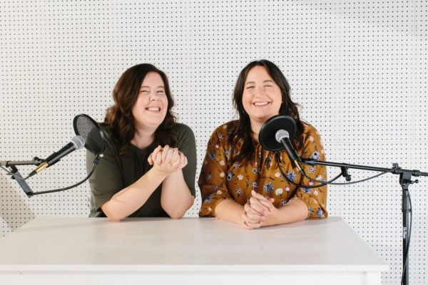 Helen and podcast partner Caroline sitting at a white table behind microphones