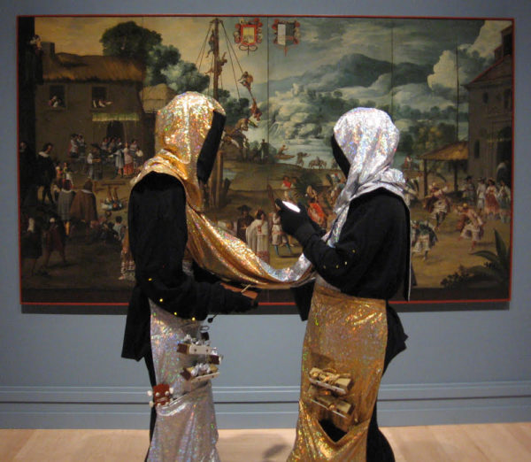 Two people standing in front of a large colorful fine art painting. They are facing each other and completely covered in black with gold and silver headcoverings, aprons, and a tube connecting them.