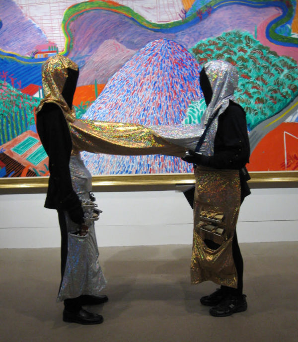 Two people standing in front of a large colorful fine art painting. They are completely covered in black with gold and silver headcoverings, aprons, and a tube connecting them.