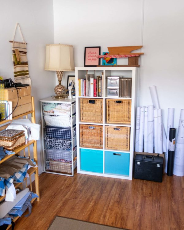 A tidy corner with fabric in drawers, and a cubby with books and wicker baskets inside.
