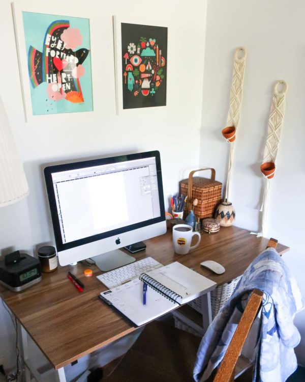 Corner desk with an Apple computer, open notebook, coffee mug and other desk tools on top. There are pretty prints on the wall above and macrame wall hangings to the right.