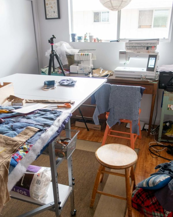 View of a sewing table with a project on top. In the background are a tripod in front of a table with a serger and sewing machine on it.