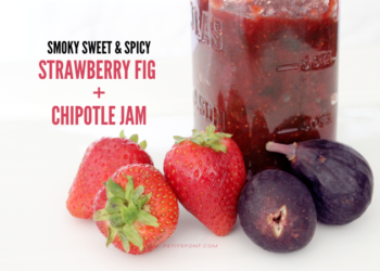 "A jar of red jam on a white background with intact strawberries and figs in front of it. Text overlay reads ""smoky sweet & spicy strawberry fig and chipotle jam"""