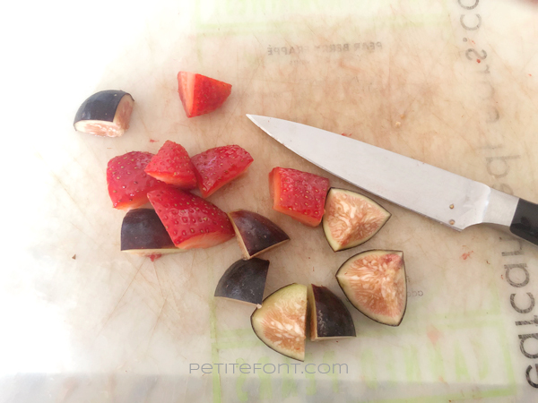 Chopped strawberries and figs on a cutting board with a small knife
