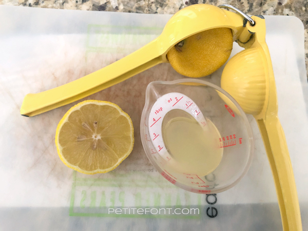Half lemon sitting on a flexible cutting board with a hand juicer and an ounce of juice in a mini measuring cup