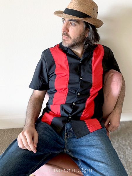 Ryan sitting in a pink chair against a white wall wearing a straw hat, red and black colorblocked bowling shirt, and blue jeans.