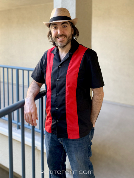Ryan leaning against a blue railing wearing a straw hat, red and black colorblocked bowling shirt, and blue jeans.