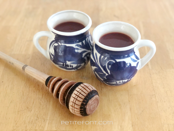 2 cups of champurrado in white mugs with a blue design, sitting on top of a wooden table next to a Mexican whisk called a molinillo