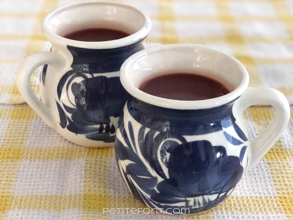 2 cups of champurrado in white mugs with a blue design, sitting on top of yellow and white check tea towels