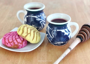2 cups of champurrado in white mugs with a blue design, sitting on top of a wooden table next to a plate of Mexican pastries and a Mexican whisk called a molinillo