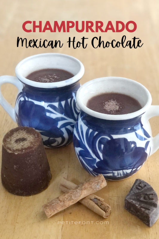 2 cups of champurrado in white mugs with a blue design, sitting on top of a wooden table. In front of the mugs are a used cone of piloncillo, 2 cinnamon sticks, and a wedge of Mexican chocolate