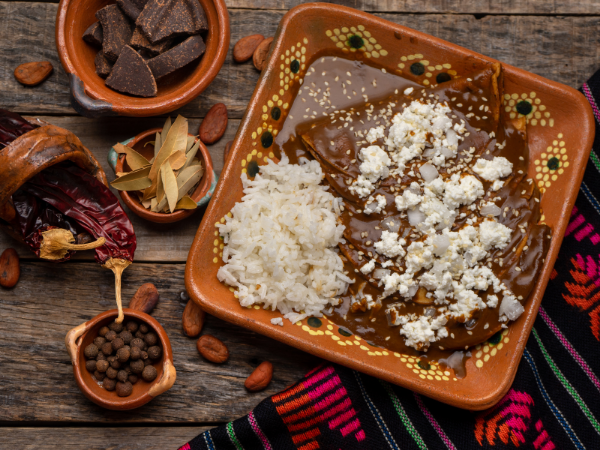 A bowl of dark mole topped with Mexican cheese next to white rice. Other ingredients such as chocolate, chiles, and nuts are on the table around the bowl