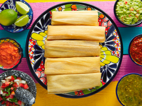 A bowl of wrapped tamales surrounded by smaller bowls of salsas, gauacamole, and limes