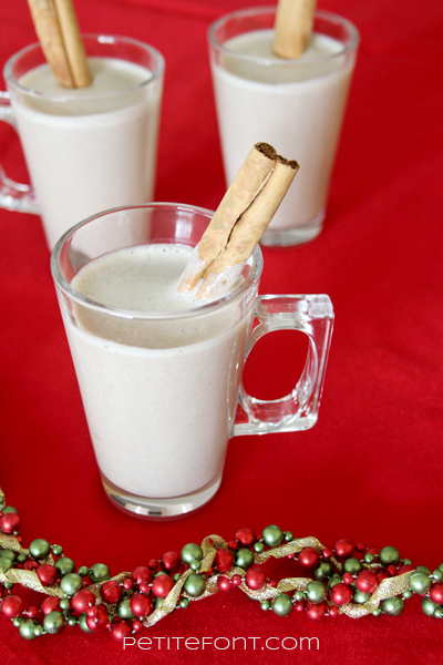 3 cups of coquito on a red background with Christmas garland around